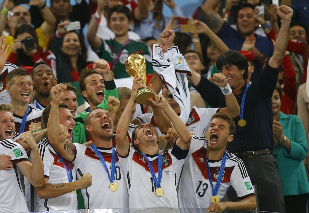 Germany's captain Philipp Lahm lifts the World Cup trophy as he celebrates with his teammates after the 2014 World Cup final between Germany and Argentina at the Maracana stadium in Rio de Janeiro July 13, 2014. REUTERS/Kai Pfaffenbach (BRAZIL - Tags: SPORT SOCCER WORLD CUP) - RTR3YGR1