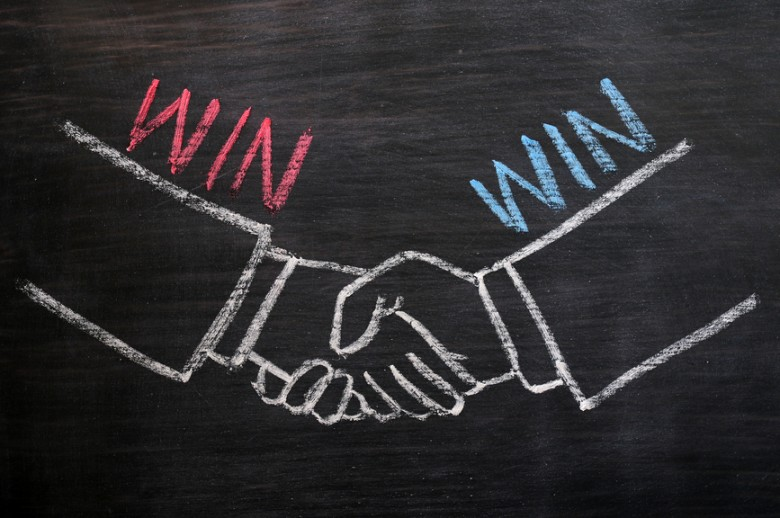 Mutual benefit or win-win concept of handshaking drawn with chalk on a blackboard
